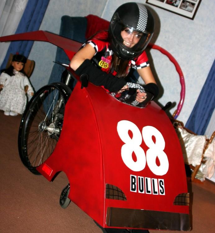 Chica en silla de ruedas disfrazada de carro de carreras
