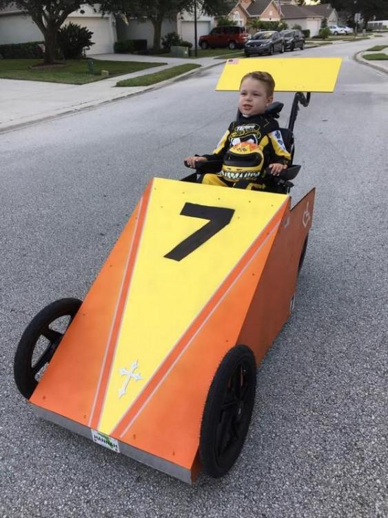 Niño disfrazado de un auto de carreras en su silla