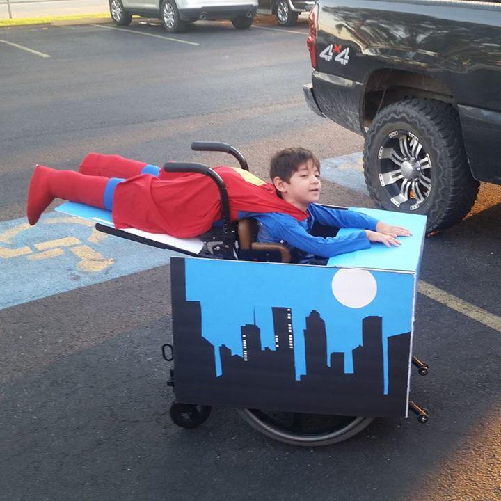 Niño en su silla de ruedas disfrazado de superman volando en la ciudad