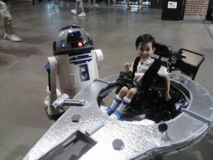 Niño disfrazado de una nave espacial en su silla de ruedas