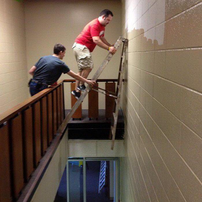 Personas en una escalera intentando pintar