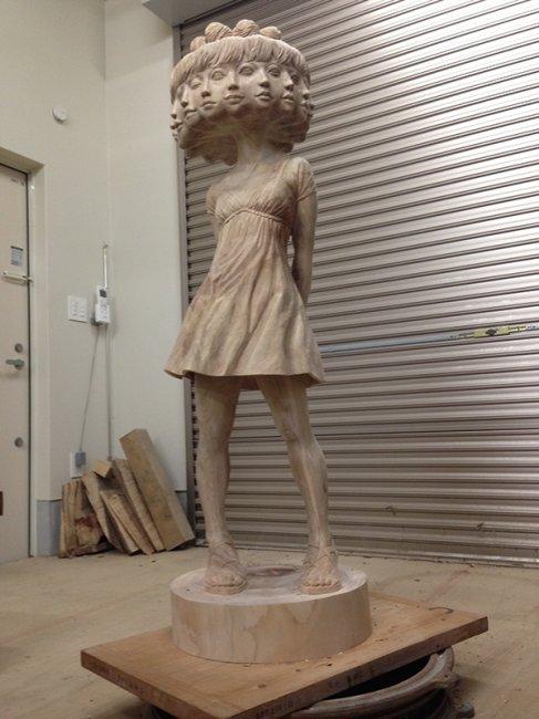Escultura de madera de una niña con muchas cabezas
