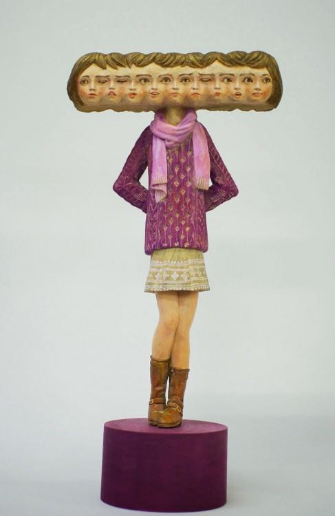 Escultura de niña con mucha cabezas