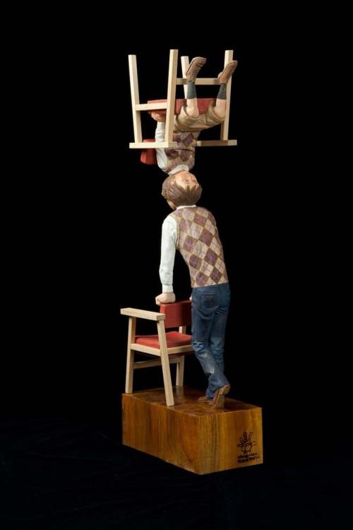 Escultura de un niño sobre la cabeza de otro