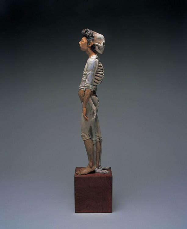 Escultura de una persona con un esqueleto detrás