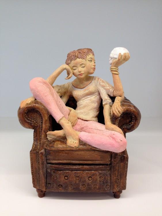 Escultura de una chica sentada en un sillón con un cráneo en la mano