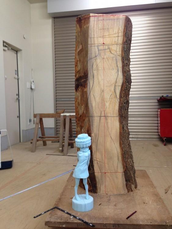 Tronco de madera con un boceto de la escultura