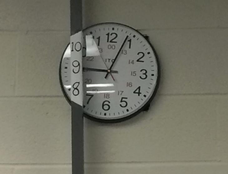 Reloj de pared detrás de un tubo de hierro