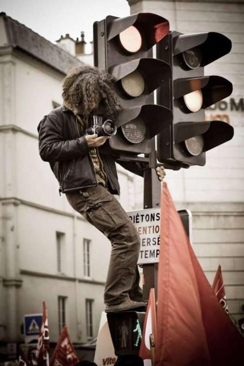 Fotógrafo arriba de un semáforo