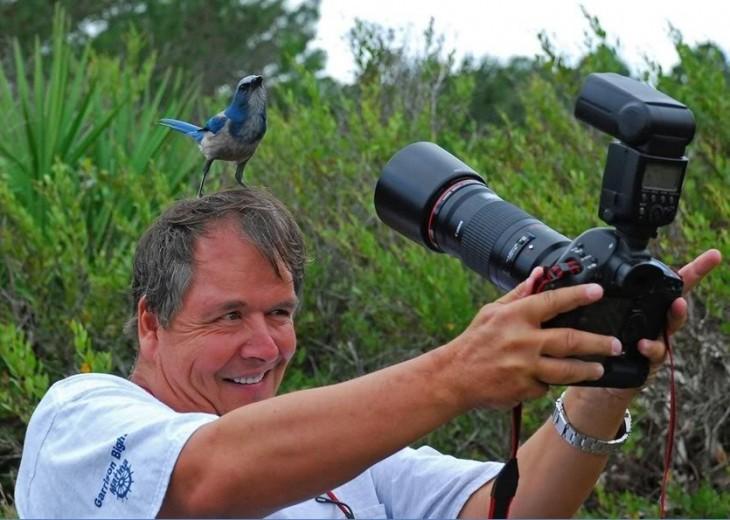 Fotógrafo tomando foto de un pájaro en su cabeza