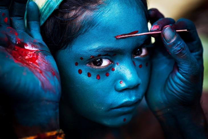 Manos pintando la cara de una niña