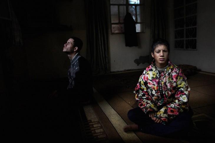 Dos chicos sentados en una habitación oscura
