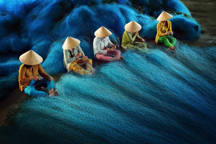 Personas en el suelo tejiendo algo azul