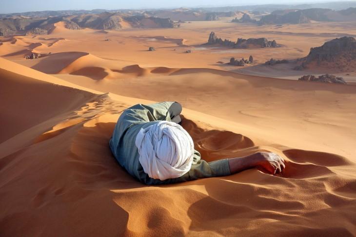 Hombre acostado en el desierto del Sahara
