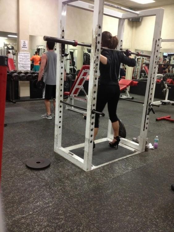 chica con tacones en un gimnasio levantando pesas