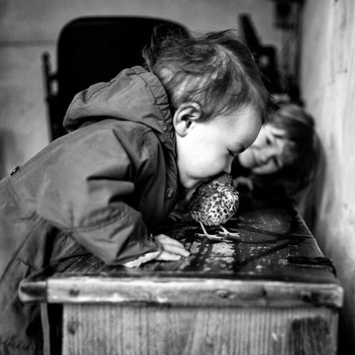 Niño besando a un pájaro