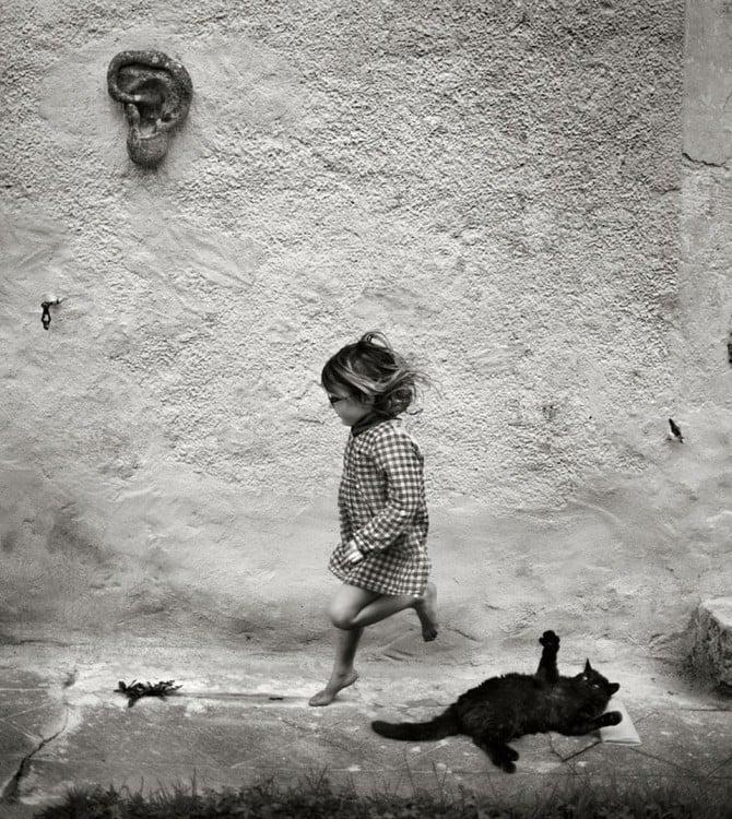 Niña brincando con un gato negro