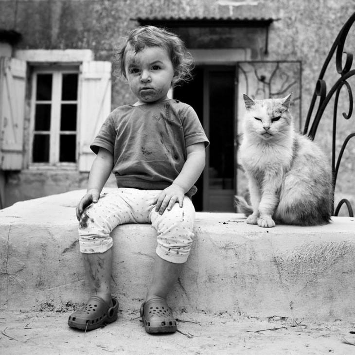 Niño lleno de lodo a un lado de un gato