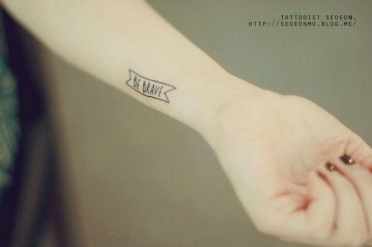 Tatuaje minimalista con frase en el brazo de una persona
