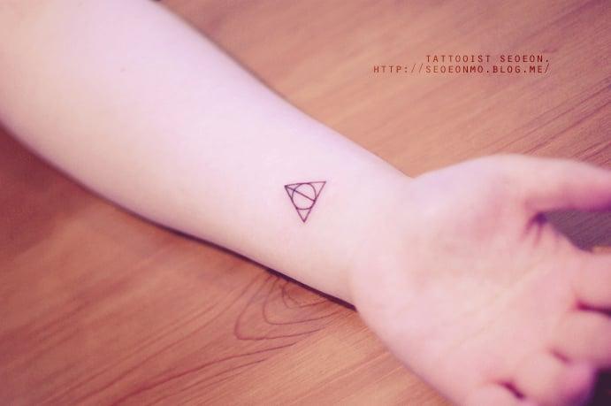 Tatuaje minimalista de triángulo en una mano