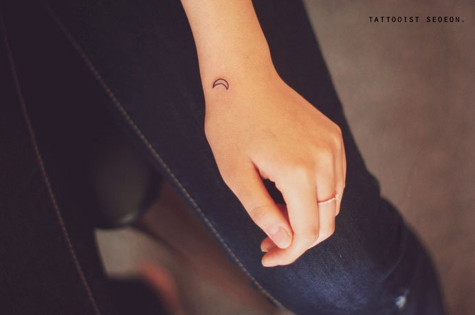 Tatuaje minimalista de luna en la muñeca de una persona