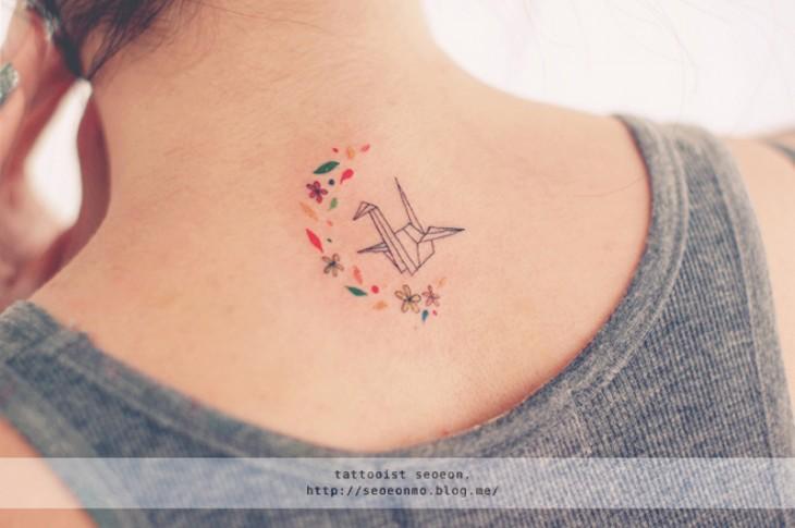 Tatuaje minimalista de origami en el cuello de una chica