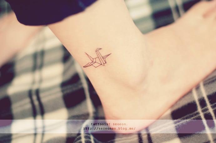 Tatuaje minimalista de origami en el pie de una chica