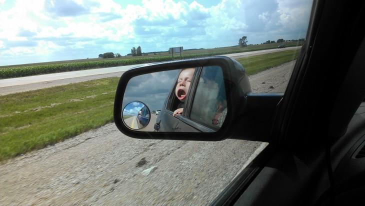 Niño reflejado en espejo de un auto
