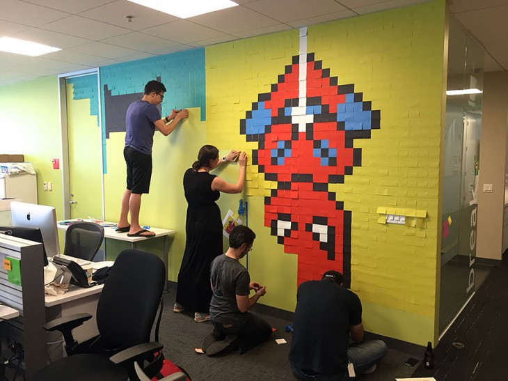 Personas creando un mural con post-it