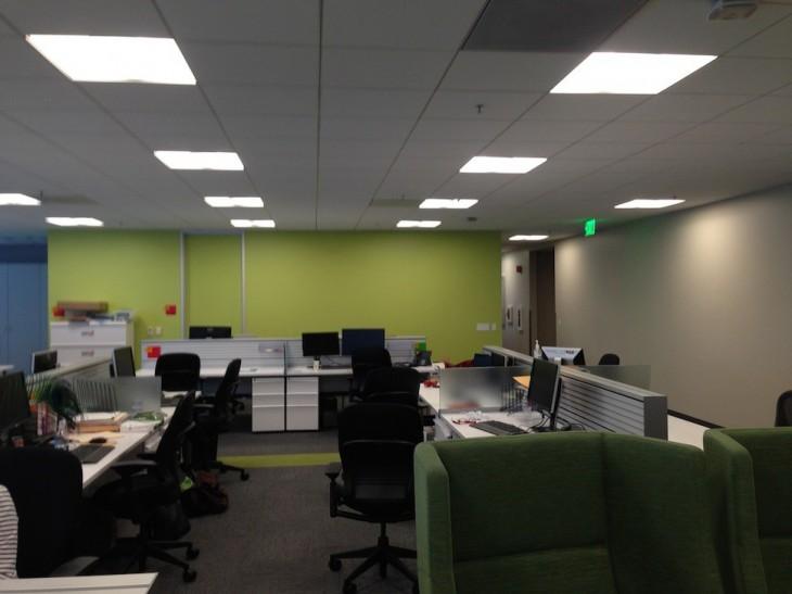 Oficina con sillas y computadoras en color verde sin ninguna persona dentro