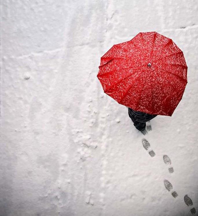 Persona usando un paraguas de corazón rojo