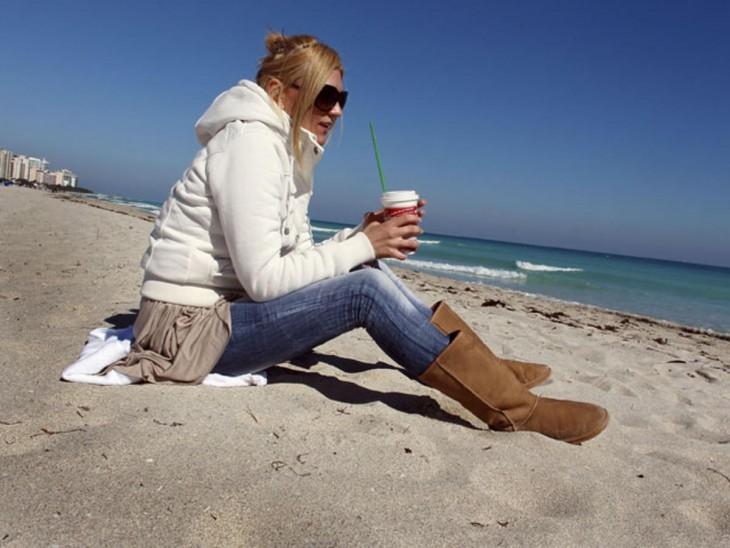 Chica en la playa con mucha ropa