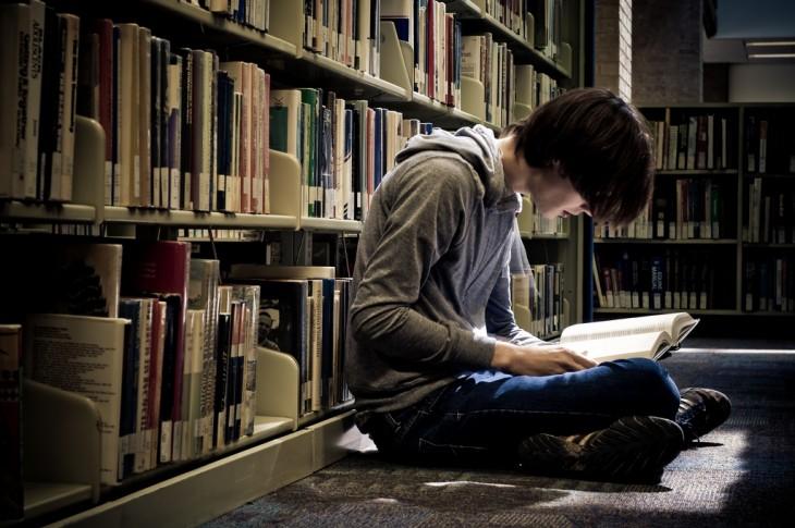 chico leyendo en el pasillo de una biblioteca