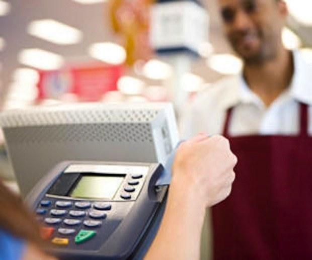 Persona deslizando una tarjeta de crédito