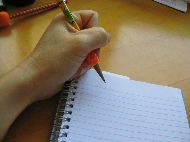 Mano con un lápiz sobre un cuaderno con espiral