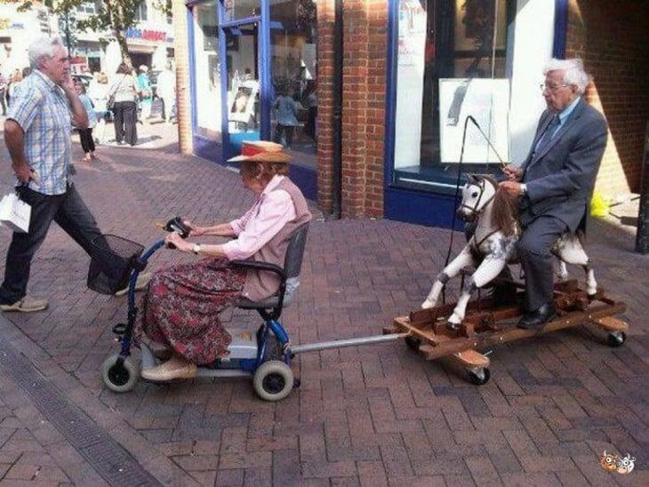 anciana emolca a anciano en vehiculos artesanales