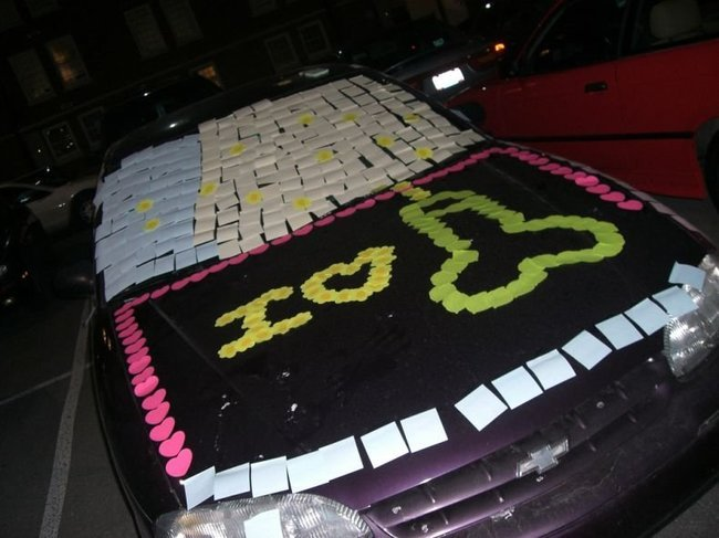 papelitos pegados en el cofre de un carro de color negro formando un mensaje