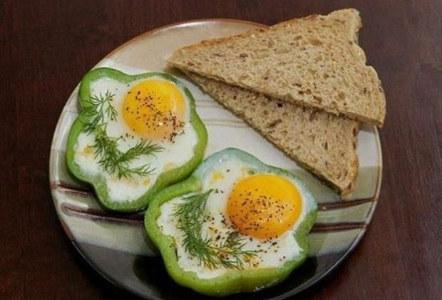 desayuno de huevos y pan tostado con pimientos verdes