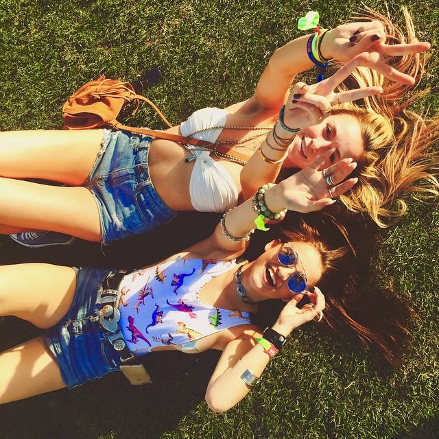 mujeres con short viendo hacia el cielo en el festival coechella