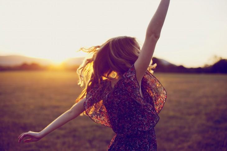 mujer feliz viendo hacia el sol