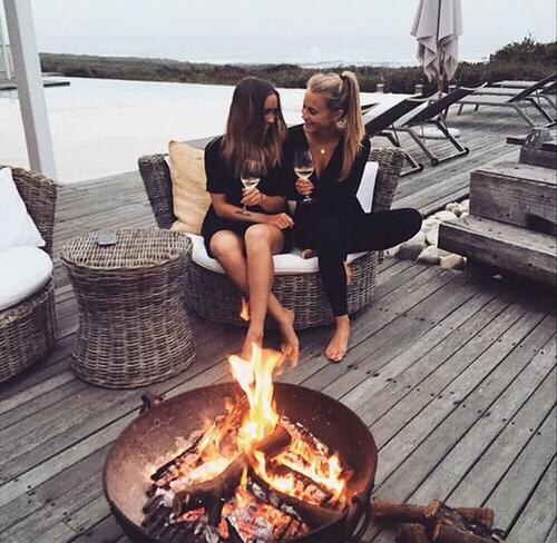 amigas tomando champagne frente al fuego