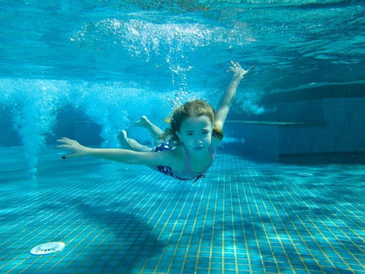 niña nadando bajo la pisicna