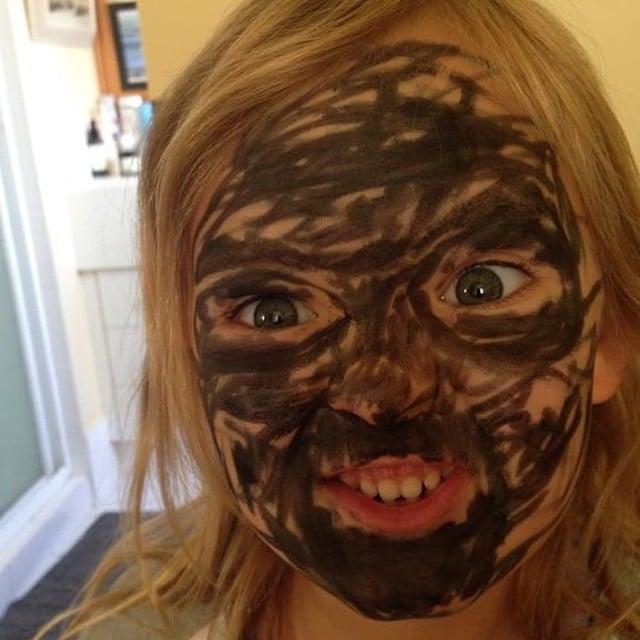 niña se mancha la cara con plumón negro a manera de maquillaje