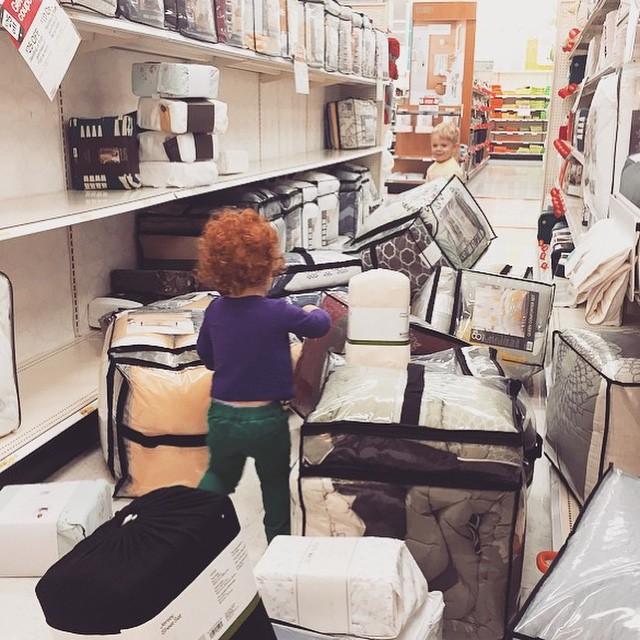niños sacan de cajon todos los cobertores y vestimenta de cams en un supermercado