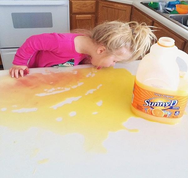 Niña tomando jugo derramado en la mesa como un perrito
