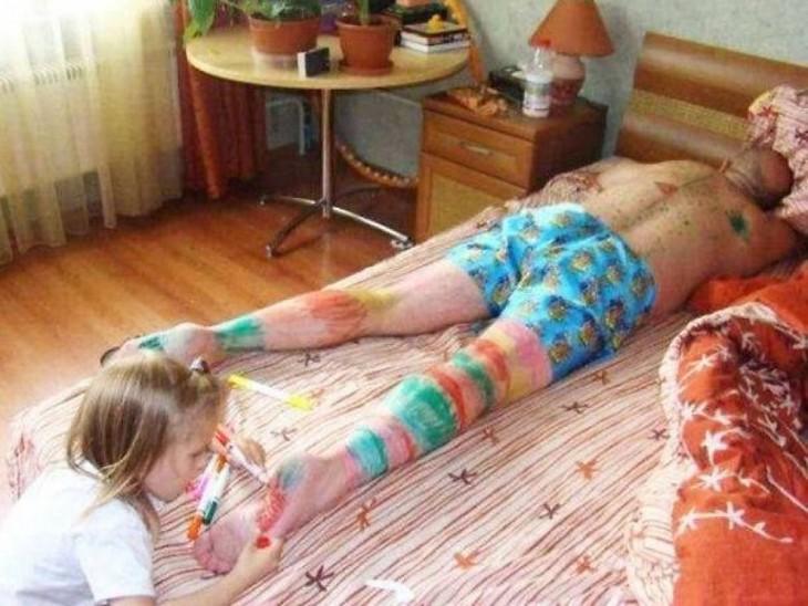 arcoiris dibujado en las piernas de hombre que al parecer esta seindo pintado por su hija