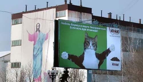 publicidad de gato y jesus con los brazos abiertos