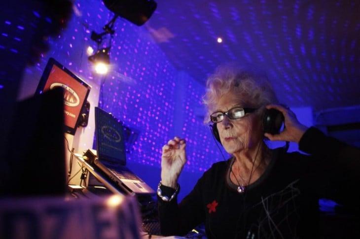 abuela practicando ser DJ en discoteca