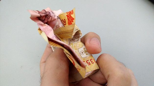 dinero hecho bola en la mano de un hombre