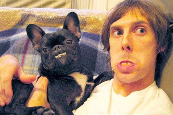 dueño muestra los dientes como su perro bulldog francés